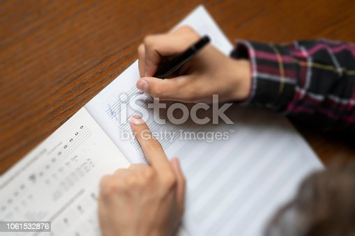 close up student hands write down music notes on class in school
