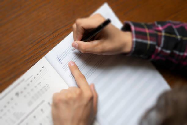 nahaufnahme der student hände notieren sie musiknoten auf klasse in der schule f - one song training stock-fotos und bilder