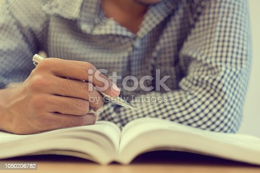close up student man hand holding pen for guideline reading on text book at campus library for examination education concept