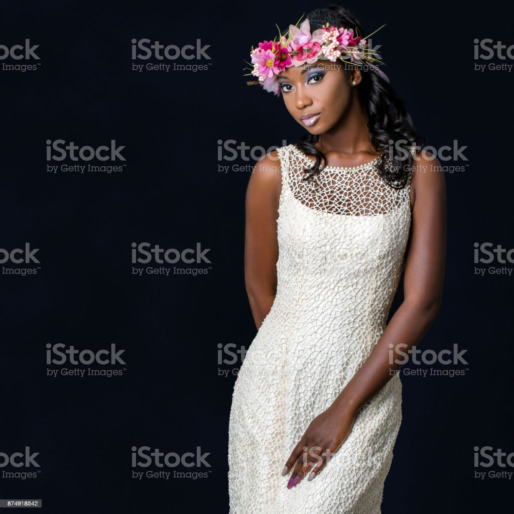 Close up studio portrait of attractive young african bride wearing white wedding gown. Medium shot of girl with colorful flower garland against dark background. stock photo