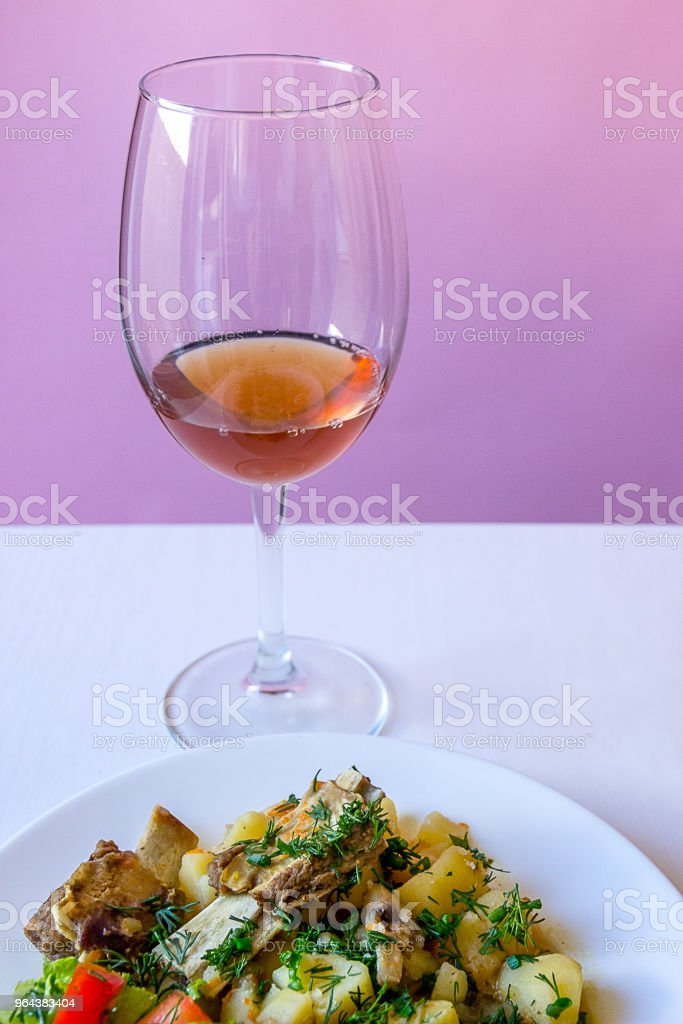 Close-up de batata recheada com costelas de vitela e salada fresca e vidro de cipó-de-rosa - Foto de stock de Almoço royalty-free