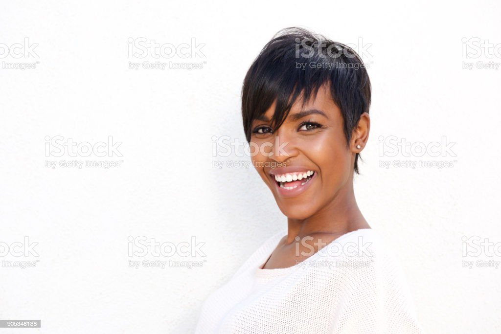 Close up stylish young black woman laughing against white background stock photo