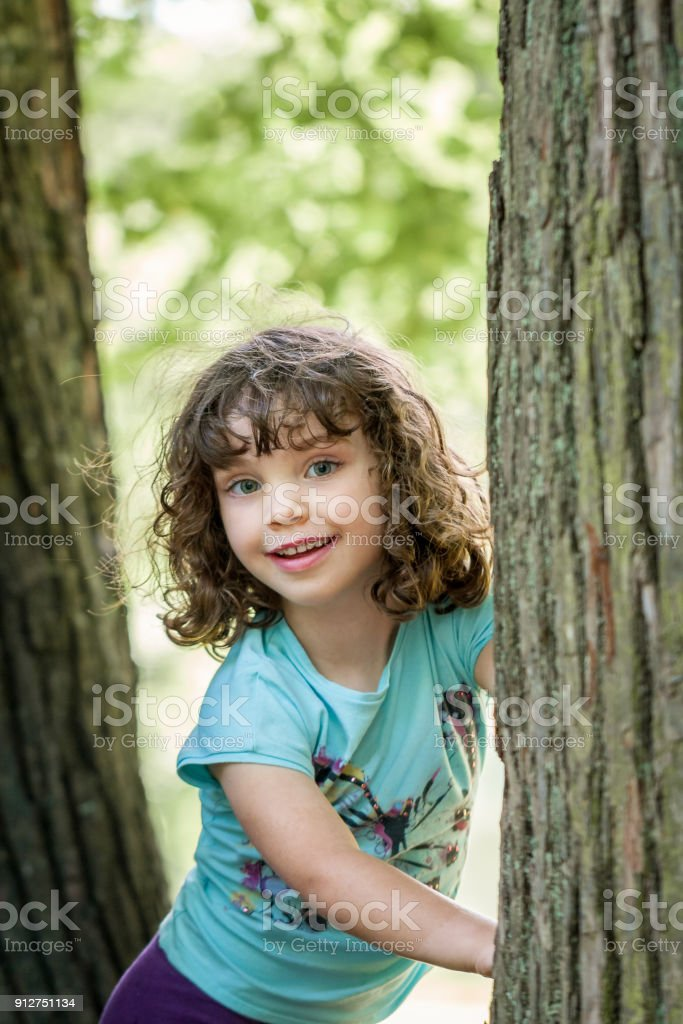 Close up summer portrait of a cute pretty smiling girl next to trees. royalty-free stock photo