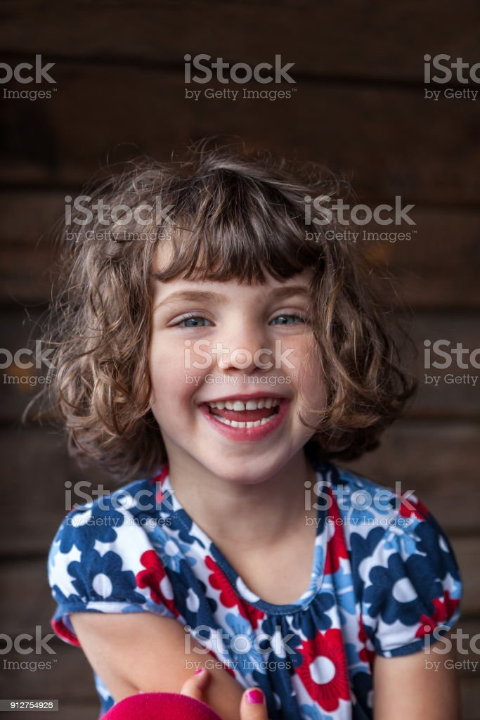 Close up summer portrait of a cute pretty smiling preschool girl with tangled hair stock photo