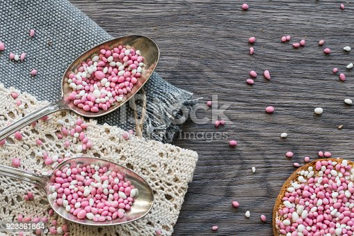 istock close up table scene with two vintage silver spoons with rusk, typical Dutch food muisjes, pink and white aniseed, for announcement birth of a daughter, baby girl 923861864