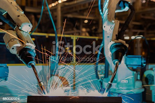 istock Close up team robots are welding in factory 680032024