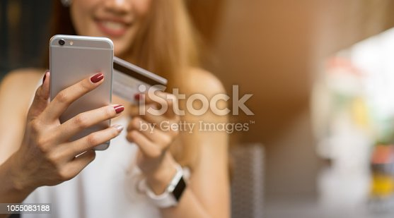 close up teenage girl using smartphone for choose or search or order product from marketplace website and pay by credit card at office , modern lifestyle and shopping concept