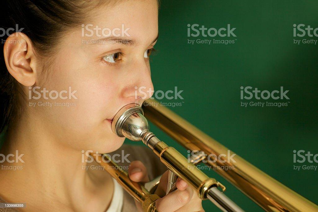 close up: teenager girl practice the trombone stock photo