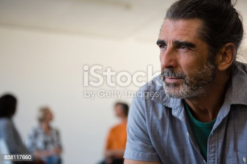 istock Close up tensed man with friends discussing in background 838117660