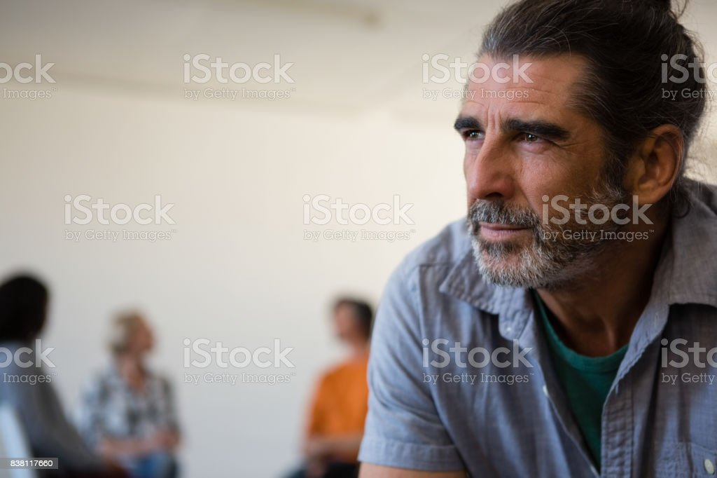 Close up tensed man with friends discussing in background stock photo
