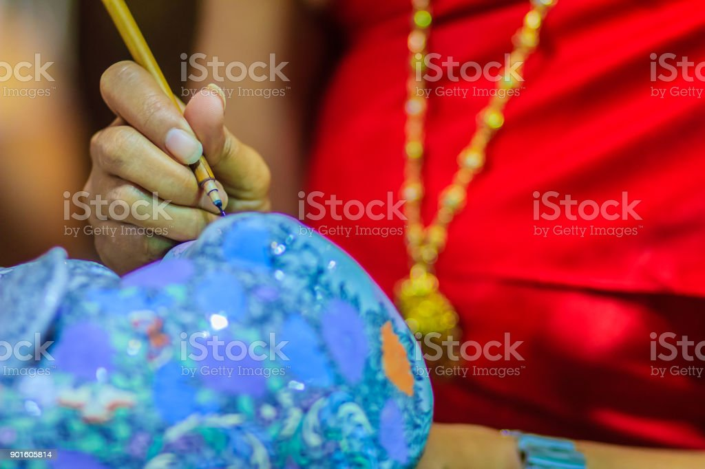Close up Thai woman artist in red Thai style dressed is painting the masterpiece of Benjarong pattern, the famous 5- colored porcelain ceramic wares. stock photo