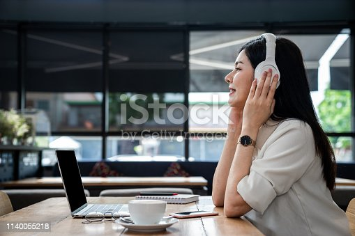istock Close up the an Asian girl is freelancer woman, she is listening online music and using the laptop computer and driking a cup of coffee on morning in a coffee shop or her office. 1140055218
