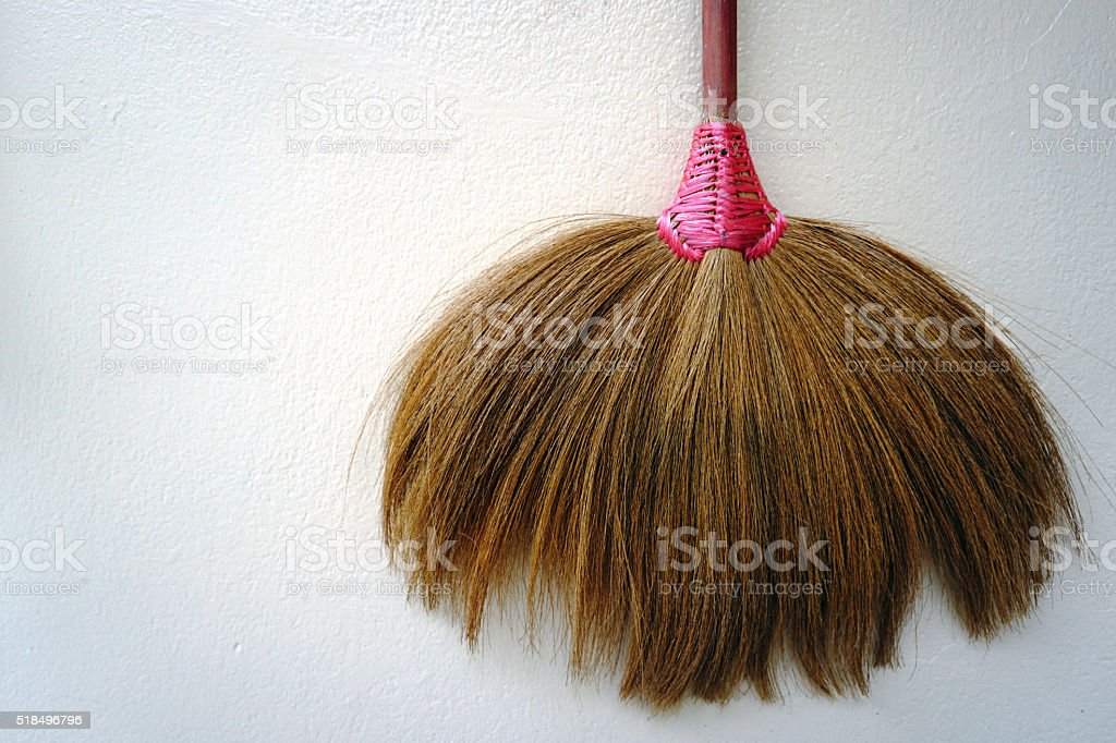Close up the broom.with a white old wall. stock photo