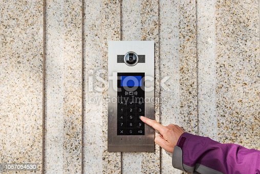 istock Close up the female hand presses the doorphone button 1057054530