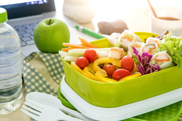 Close up the green Lunch box on work place of working desk ,Healthy eating clean food habits for diet and health care concept stock photo