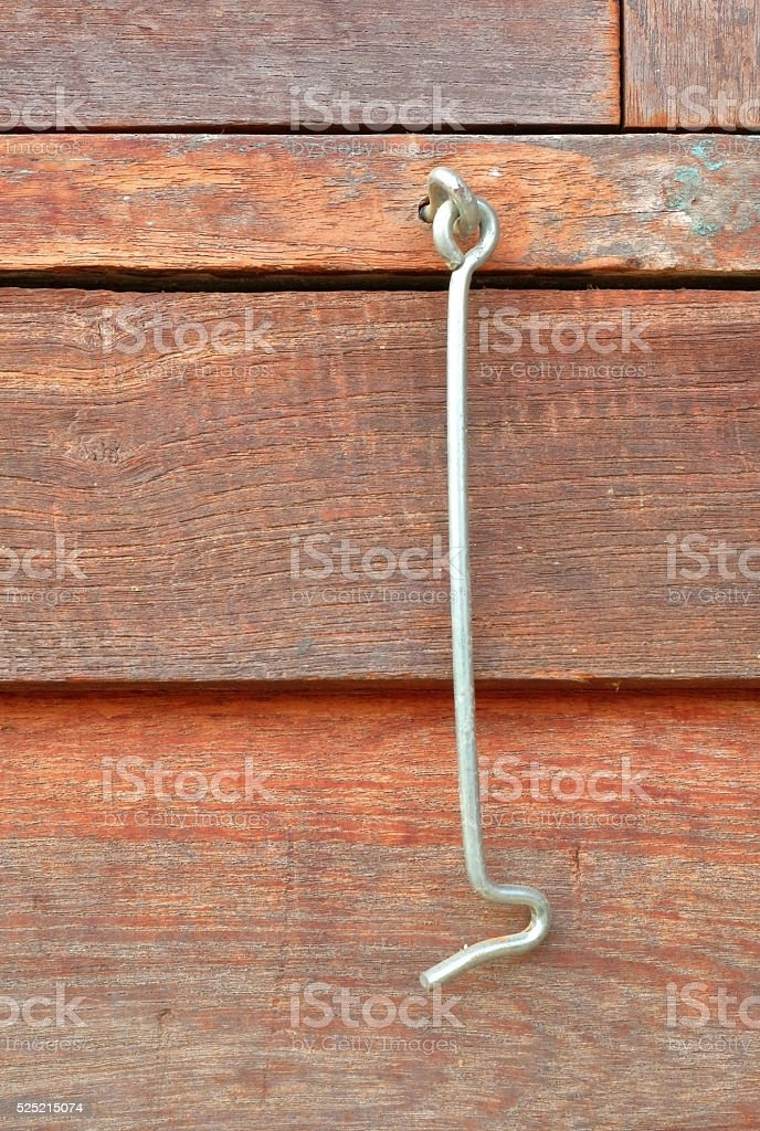 Close up the old metal window hook with wooden background. stock photo