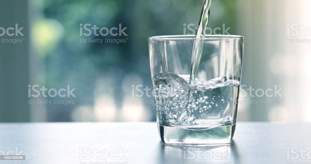 Close up the  pouring purified fresh drink water from the bottle on table in living room
