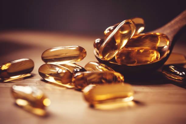 i̇yi beyin, kalp ve sağlık yeme yararı için ahşap plaka üzerinde d vitamini ve omega 3 balık yağı kapsüller takviyesi kapatın - vitamin d stok fotoğraflar ve resimler