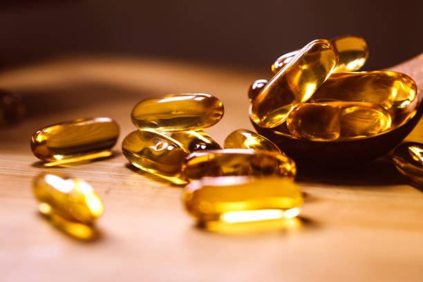 Schließen Sie die Vitamin D und Omega 3 Fischöl Kapseln Ergänzung auf Holzplatte für gutes Gehirn, Herz und Gesundheit Essvorteil – Foto