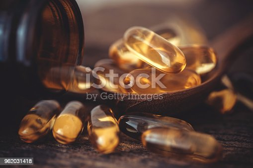 istock Close up the vitamin D and Omega 3 fish oil capsules supplement on wooden plate for good brain , heart and health eating benefit 962031418