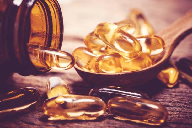 Nahaufnahme der Vitamin D und Omega-3 Fischöl Kapseln Ergänzung auf Holzplatte für gutes Gehirn, Herz und Gesundheit Essen nutzen – Foto