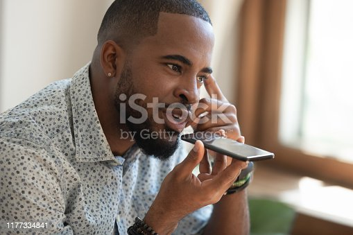 Close up thoughtful mindful african american guy sitting on couch, talking on speakerphone, dictating voice message, using online translator app or voice recognition software, virtual assistant.