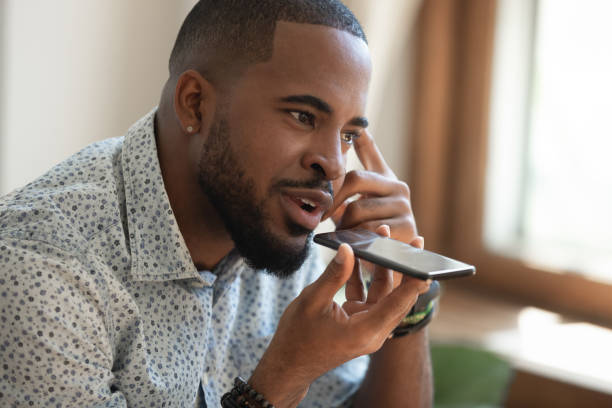 Close up thoughtful african american guy using virtual assistant. Close up thoughtful mindful african american guy sitting on couch, talking on speakerphone, dictating voice message, using online translator app or voice recognition software, virtual assistant. conference phone stock pictures, royalty-free photos & images