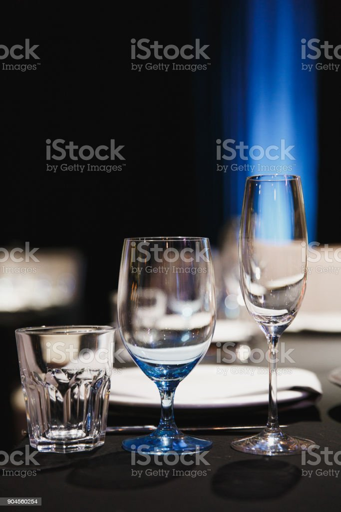 Close up three glasses, forks, knives, napkins, candles and decorative flower on dark black tablecloth on table served for dinner in cozy restaurant. Empty served restaurant table with wine glass. stock photo
