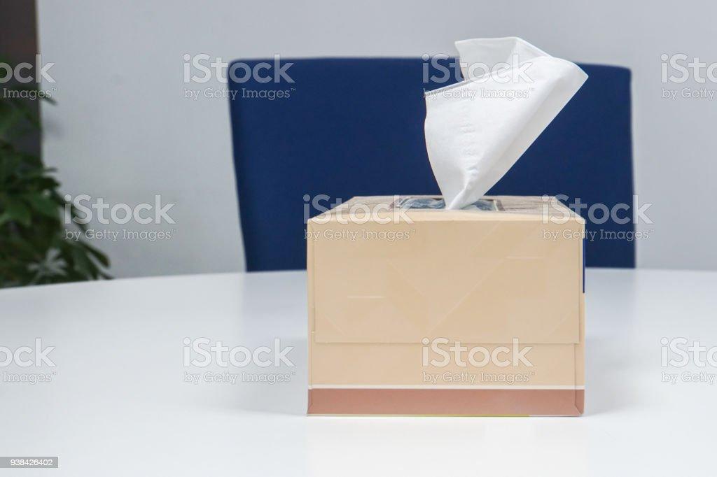 Fermez la boîte de mouchoir en papier sur la table de bureau blanc