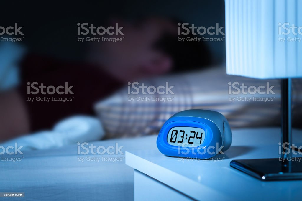 Close up to digital alarm clock on nightstand in bedroom. Man sleeping in bed in the background. stock photo