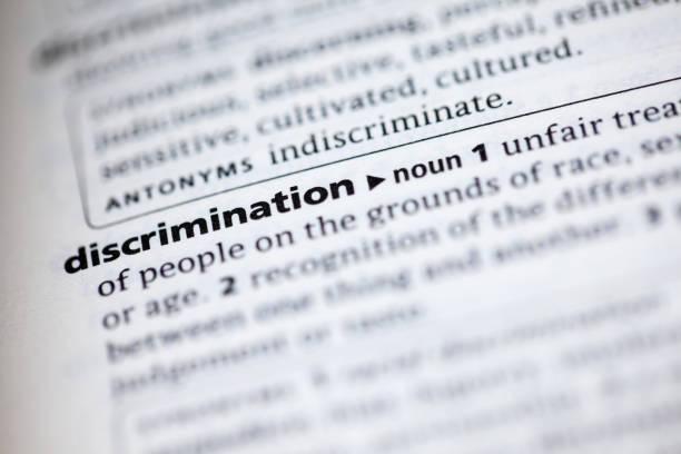 nahaufnahme der wörterbuch-definition des wortes diskriminierung - vorurteil stock-fotos und bilder