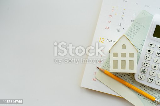 close up top view group of calculator , home model ,yellow pencil, banking account book and calendar on white color background with space for money management ,home loan and personal financial concept