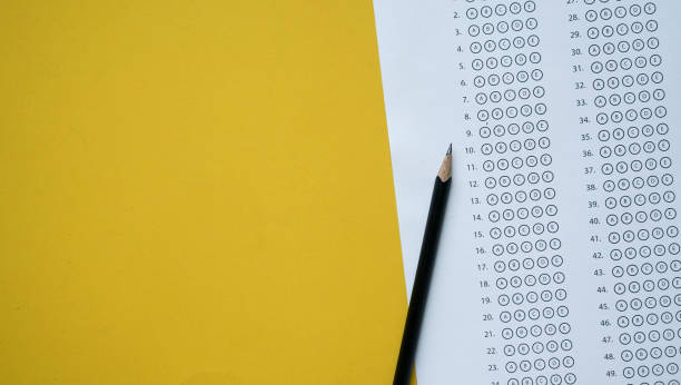 close up top view of black pencil over exam answer sheet paper with multiple choice on yellow background for world literacy day and education concept - exam stock pictures, royalty-free photos & images