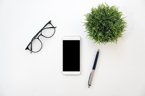 close up top view of black screen smartphone,pen,glasses and little plant on white table background for mockup design modern lifestyle stationary concept
