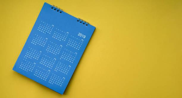 draufsicht der blauen farbe kalender neujahr 2019 auf gelbem hintergrund mit exemplar für design-element-konzept hautnah - donnerstagnachmittag stock-fotos und bilder