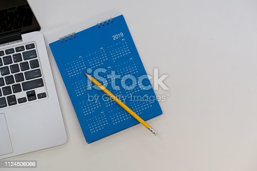 1073023470istockphoto close up top view of blue color calendar new year 2019 with laptop and yellow pencil on white table background with copyspace for design element concept 1124506066