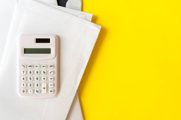 close up top view of calculator with mail invoice letters on yellow color background for utility and lifestyle monthly expense concept close up top view of calculator with mail invoice letters on yellow color background for utility and lifestyle monthly expense concept aisne stock pictures, royalty-free photos & images