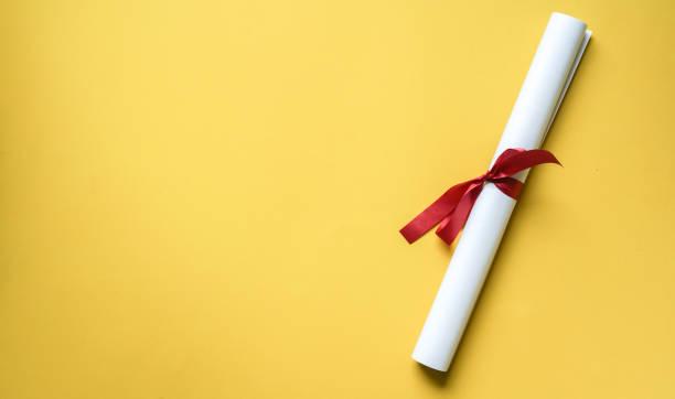 close-up bovenaanzicht van gecertificeerde graad op gele achtergrond voor onderwijsconcept - diploma stockfoto's en -beelden