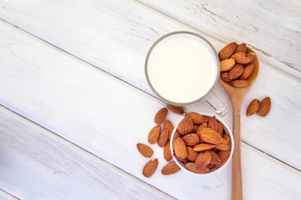 Draufsicht der gesunde Mandelmilch in das Trinkglas mit Samen in weiße Tasse und Löffel aus Holz auf weißen hölzernen Tischplatte mit textfreiraum hautnah – Foto