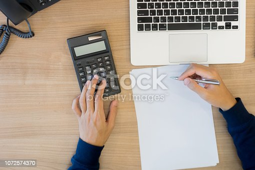 502086873 istock photo close up top view of man hand press on calculator counting calculating about monthly expense and writing list to paper ,money management concept 1072574370