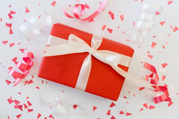 großaufnahme draufsicht des rot-geschenk-box-verpackung mit schleife gebunden und gruppe von rollen band mit konfetti auf weißem hintergrund für geburtstag, valentinstag, frohe weihnachten, frohes neues konzept - laminat günstig stock-fotos und bilder