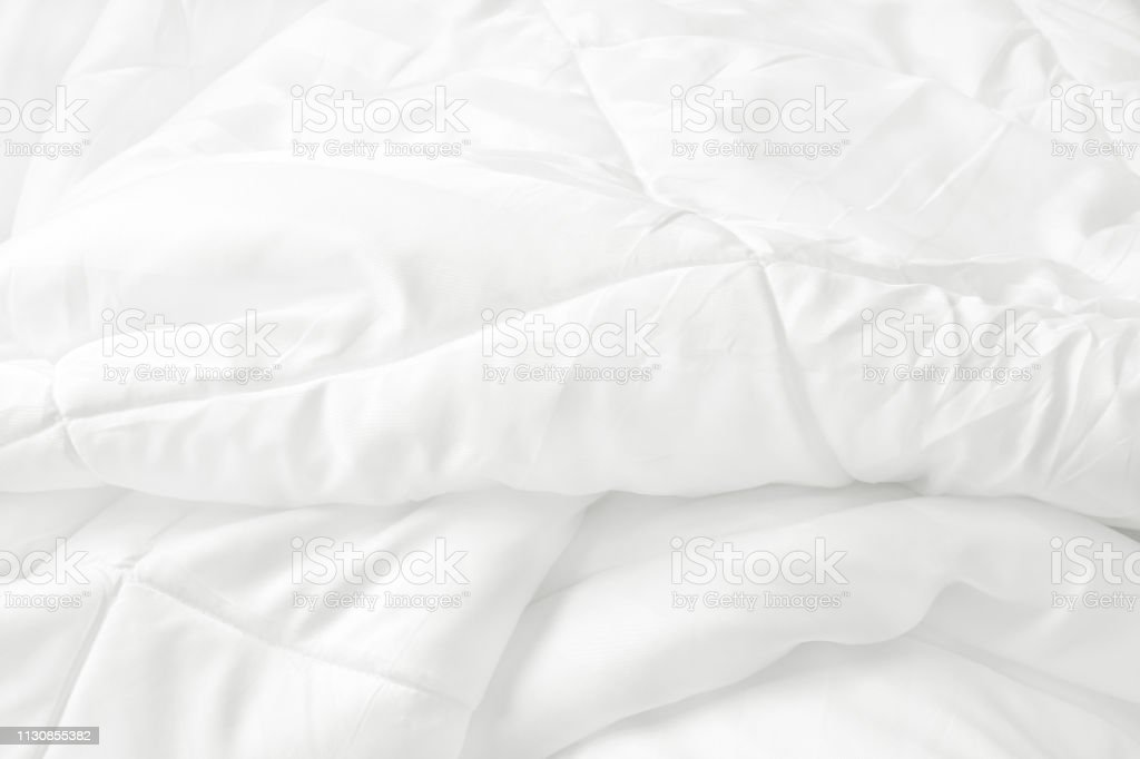 Close up top view of white bedding sheet and wrinkle messy blanket in...