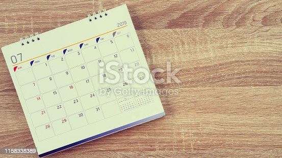 1027407218 istock photo close up top view of white color calendar July 2019 standing on wood table at outside for make appointment or remind important date,business office supply concept 1158338389
