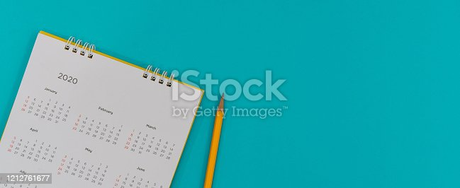 istock close up top view on white calendar  2020 schedule with yellow pencil on blue color background to make appointment meeting or manage timetable each day for design planning work and life concept 1212761677