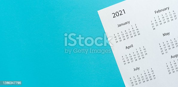 close up top view on white calendar 2021 schedule on blue color background to make appointment meeting or manage timetable each day for design planning work and life concept