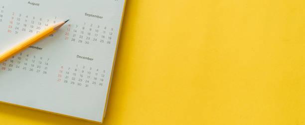 sluiten omhoog hoogste mening op witte kalender met potlood en maandschema om benoemingsvergadering te maken of tijdschema elke dag te beheren legt op gele kleurenachtergrond voor het plannen van het werk en het levensconcept - december stockfoto's en -beelden