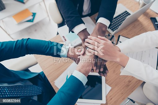 istock Close up top view portrait of arms on top of each other of professional successful corporate agents in the end of conference, conversation, sitting in work place, station, we are force together 933832544