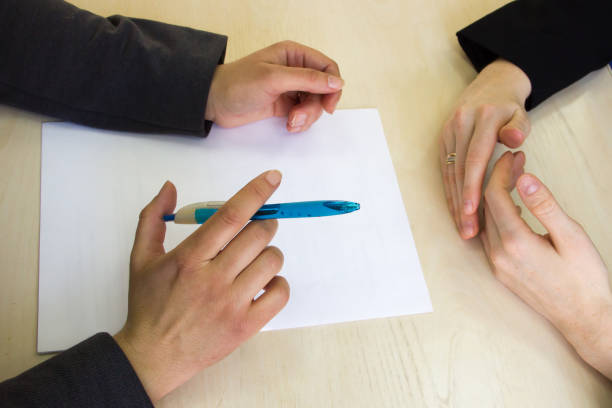 Close up top view to hands of two businesswomen that sit at table and discuss something. stock photo