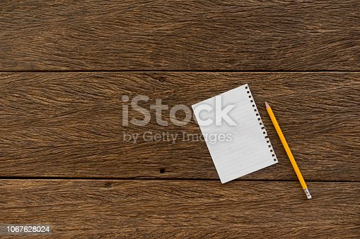 1090161334 istock photo close up torn paper note pad lay on brown wood background tabletop with yellow pencil for writing to do list in new year' misson concept 1067628024