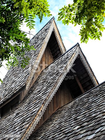 close up traditional asian roof top of building with wooden roof tiles in Phuket island, Thailand
